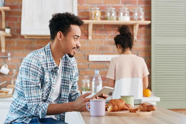 Портрет мужчины смешанной расы в клетчатой рубашке отправляет текстовое сообщение со своего цифрового планшетного компьютера, использует беспроводной интернет, Бесплатные Фотографии