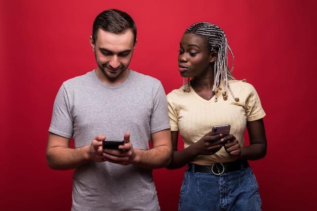 混血の男と女の顔をしかめ、赤い背景の上に分離されたお互いの携帯電話のピークの肖像画 Premium写真