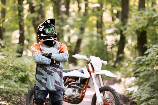フォレストでポーズをとるバイクライダーの肖像画 無料写真