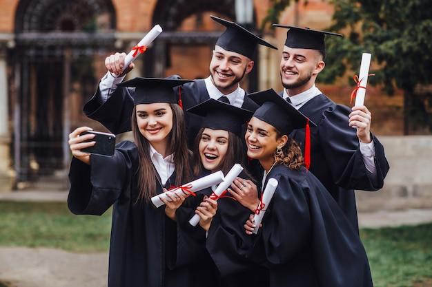 卒業証書を保持していると電話lifestuleでselfieをしている多民族の卒業生の肖像画 Premium写真