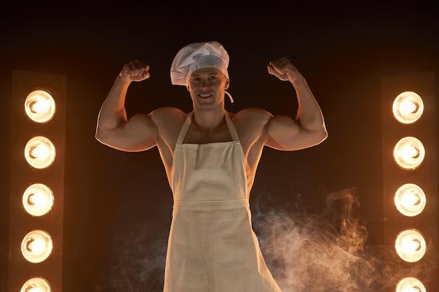 연기가 자욱한 배경 남성 주부에 강한 팔뚝 근육을 보여주는 흰색 앞치마와 요리사 모자를 쓰고 근육 요리사의 초상화. 부엌에서 남편. 잔인한 정육점. 프리미엄 사진