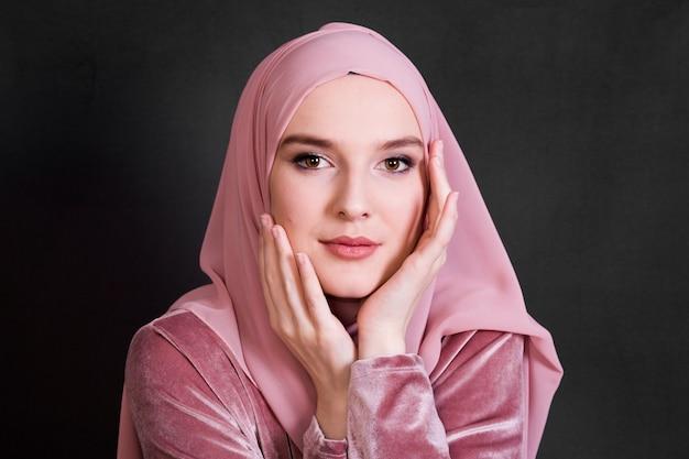 黒の背景にポーズをとってイスラム教徒の女性の肖像画 Premium写真