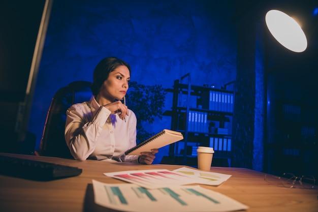 Портрет красивой привлекательной стильной опытной женщины, финансовый аналитик, исследующий данные, анализирующий отчет, соотношение заработной платы в деньгах, результат интерес инвестировать аудит, счет в ночное время, темное рабочее место Premium Фотографии