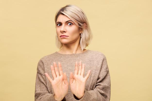 Портрет возмущенной разъяренной молодой европейской блондинки, выражающей возмущение, протягивающей руки, делающей жест «нет» или «стоп», говорящей «держись подальше от меня, пока она ругалась со своим парнем» Бесплатные Фотографии