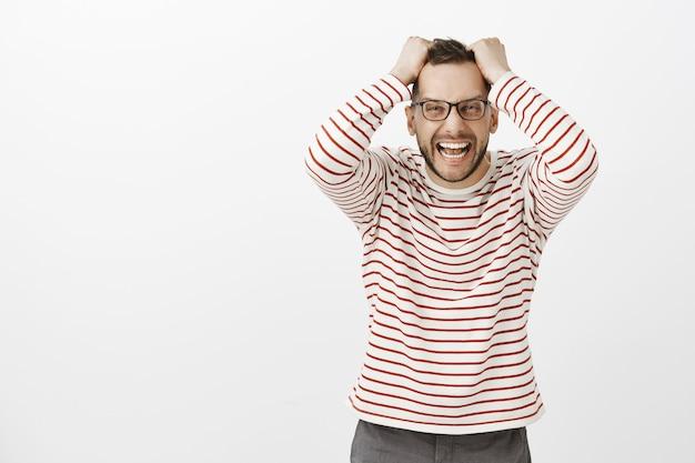 眼鏡をかけた怒った怒っている白人男性の肖像画、頭から髪を引っ張って怒りから叫んでいる、ストレスと憂鬱、怒りと灰色の壁で絶望的な気持ち 無料写真