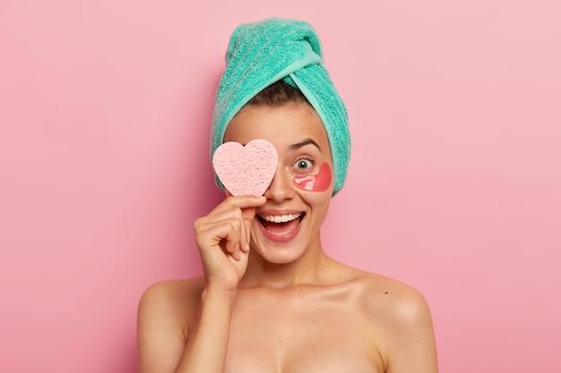 Портрет обрадованной веселой женщины держит на глазах косметическую губку, искренне смеется, носит патчи под глазами, разглаживает морщинки, ухаживает за кожей, обладает естественной красотой. Бесплатные Фотографии