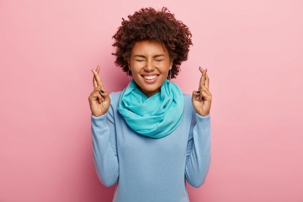 Портрет обрадованной женщины с афро-волосами, скрестив пальцы, верит в удачу, широко улыбается, носит синий свитер с шарфом Бесплатные Фотографии