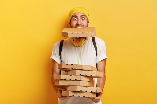 Портрет перегруженного пиццерией держит много картонных пакетов, одна во рту, носит повседневную белую футболку. Бесплатные Фотографии