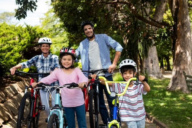 公園で自転車で立っている親と子の肖像 Premium写真