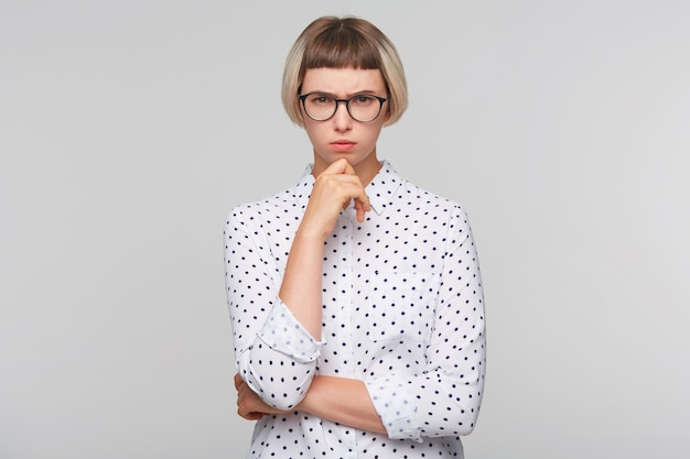 Портрет задумчивой привлекательной блондинки молодой женщины носит рубашку в горошек Бесплатные Фотографии