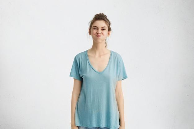 屋内で楽しんで、息を止めて、友達が彼女を笑わせようとしている間、笑いに飛び込まないように最善を尽くしている青いtシャツを着て、遊び心のある面白い10代の少女の肖像画。人間の感情 無料写真