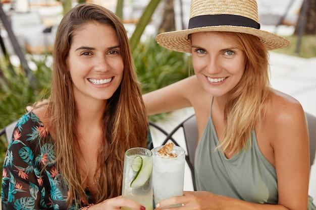 Портрет приятных на вид лучших подруг женского пола устраивает летнюю вечеринку, пьет свежие холодные коктейли. очаровательные лесбиянки чокаются напитками, празднуют начало отпуска Бесплатные Фотографии