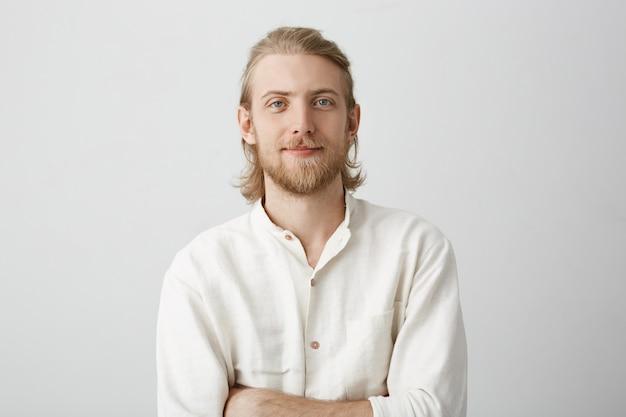 ひげと口ひげを持つポジティブなハンサムな金髪男の肖像微笑みと自信を持って白いシャツに組んだ手で立っています。 無料写真