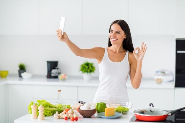 ポジティブな主婦の料理ブロガーインフルエンサーの肖像画は、彼女がヘルスケアの夕食を準備する方法を示し、彼女の有機成分を承認し、ホワイトハウスのキッチンで大丈夫サインを作ります Premium写真