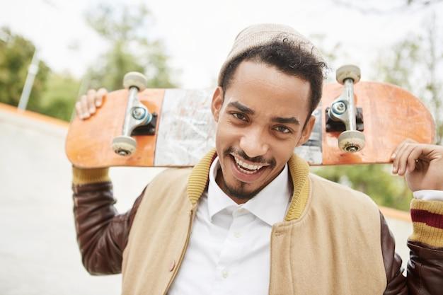 Портрет позитивного молодого подростка, практикующего катание на скейтборде на открытом воздухе, имеет счастливое выражение Бесплатные Фотографии