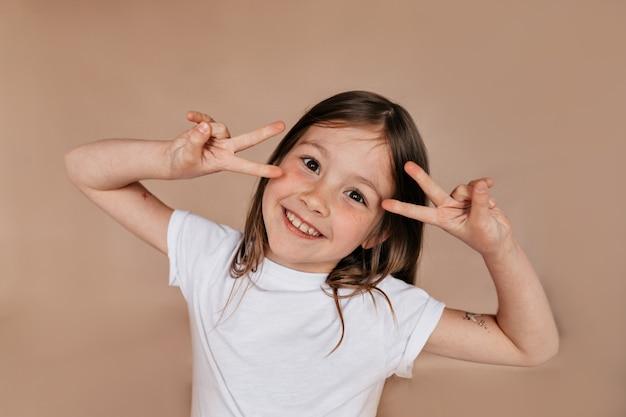 Портрет довольно очаровательной девушки, показывающей знаки мира возле лица и улыбающейся над бежевой стеной Бесплатные Фотографии