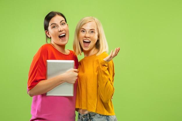 Портрет довольно очаровательных девушек в повседневных нарядах, изолированных на зеленом фоне студии. подруги или лесбиянки, использующие планшет для развлечения или оплаты. понятие лгбт, человеческие эмоции, любовь, отношения. Бесплатные Фотографии