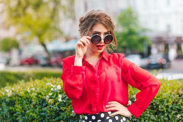 Портрет красивой девушки в солнцезащитных очках, позирует перед камерой в парке. у нее прическа, красная кофточка. Бесплатные Фотографии