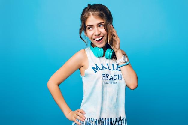 Портрет красивой девушки с длинными вьющимися волосами в хвосте, разговаривает по телефону на синем фоне в студии. на ней белая футболка, синие наушники на плечах. Бесплатные Фотографии
