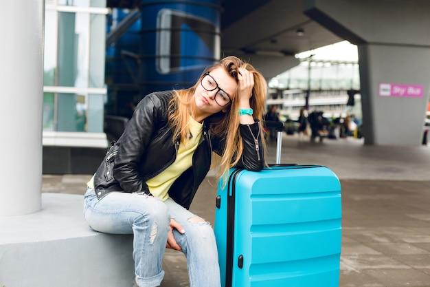 空港の外に座っているガラスの長い髪のかわいい女の子の肖像画。彼女は黄色いセーターに黒いジャケットとジーンズを着ています。彼女はスーツケースに寄りかかって待っているのに飽きてきました。 無料写真