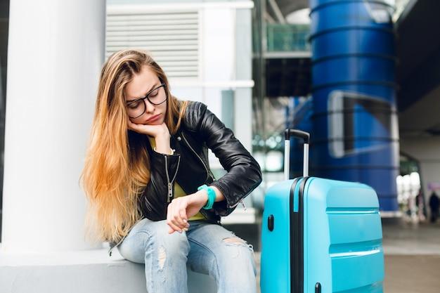 空港の外に座っているガラスの長い髪のかわいい女の子の肖像画。彼女は黄色いセーターに黒いジャケットとジーンズを着ています。彼女はスーツケースに寄りかかって時計に飽きてきた。 無料写真