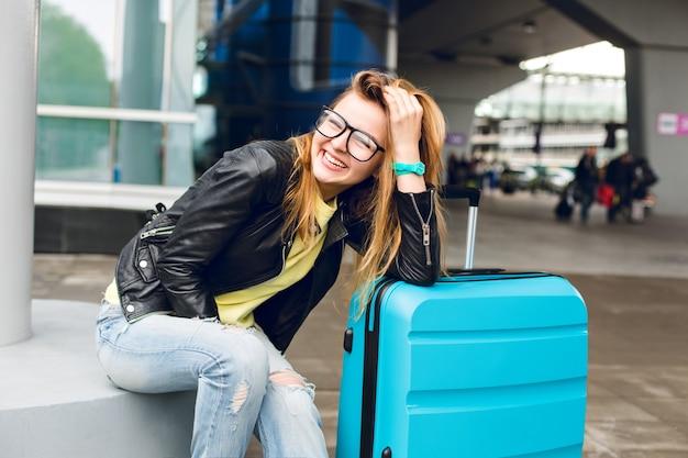 空港の外に座っているガラスの長い髪のかわいい女の子の肖像画。彼女は黄色いセーターに黒いジャケットとジーンズを着ています。彼女はスーツケースに寄りかかって、カメラに微笑んだ。 無料写真