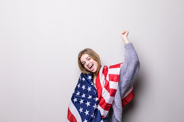 Портрет красивой девушки-подростка, держащей флаг сша, изолированный на сером. празднование 4 июля. Бесплатные Фотографии