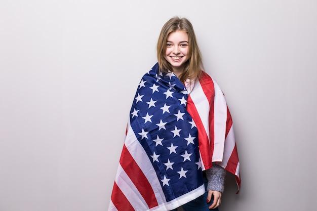 灰色に分離された米国旗を保持しているかなり十代の少女の肖像画。 7月4日のお祝い。 無料写真