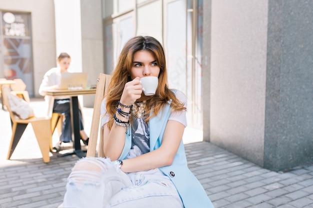 屋外のカフェで椅子に座っている長い髪のきれいな女性の肖像画 無料写真