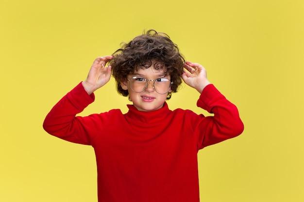 黄色のスタジオの背景に赤い摩耗でかなり若い巻き毛の少年の肖像画。子供の頃、表現、教育、楽しいコンセプト。 無料写真