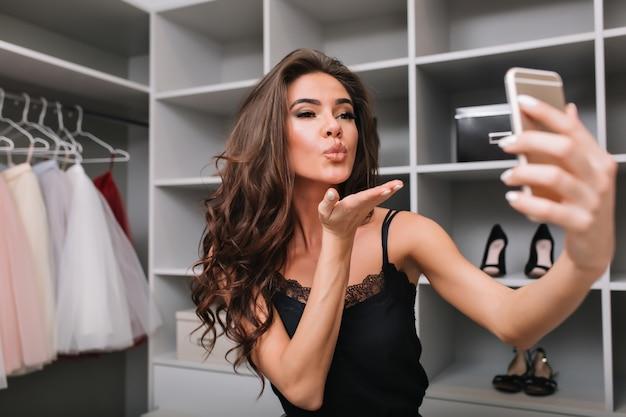 ワードローブ、ドレッシングルームでスマートフォンを使用してselfieを取っているかなり若い女の子の肖像画。彼女はキスを送っています。スタイリッシュなドレスを着て、茶色の長い巻き毛を持っています。 無料写真