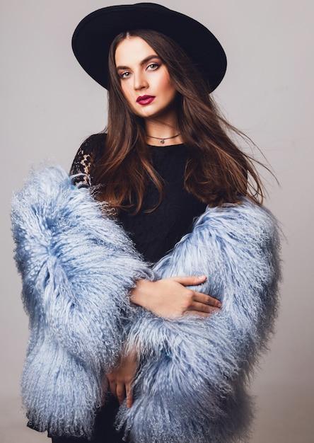 Портрет довольно молодой модели в стильном зимнем пушистом пальто и черной шляпе позирует Бесплатные Фотографии