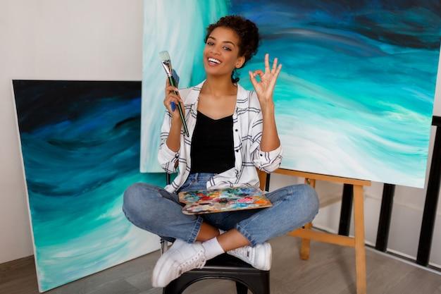 Портрет профессионального художника женской живописи на холсте в студии. женщина-художник на ее рабочем месте. Бесплатные Фотографии