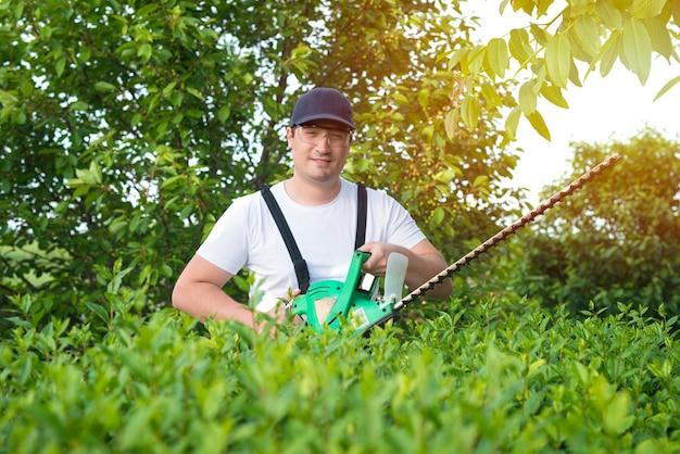 庭で働くトリマーを保持しているプロの庭師の肖像画 無料写真