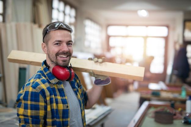 Портрет профессионального плотника средних лет с деревянной доской и инструментами, стоящего в его деревообрабатывающей мастерской Бесплатные Фотографии