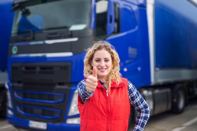 Портрет профессионального водителя грузовика показывает палец вверх и улыбается Бесплатные Фотографии