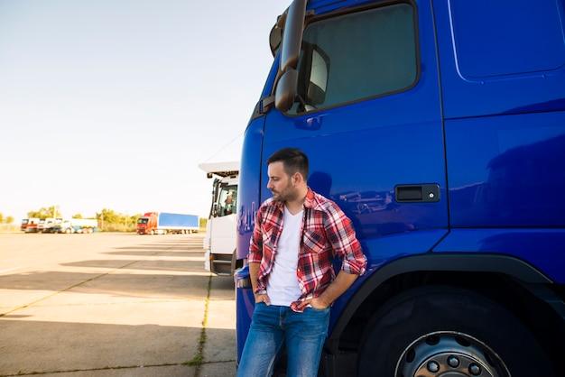 彼のトラック車両のそばに立っているプロのトラック運転手の肖像画 無料写真