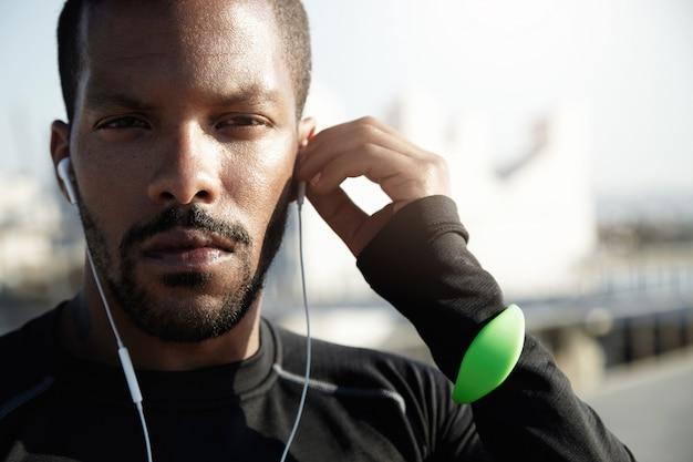힘든 운동을 위해 자신을 준비 Purposive 피트니스 트레이너의 초상화. 심각한 얼굴, 추적기, 귀에있는 헤드폰 아프리카 계 미국인 운동 선수는 스포츠에 자신을 도전하기로 결정했습니다. 무료 사진