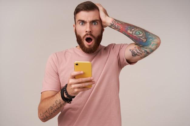 携帯電話を手に持って驚いて見て、予期しないニュースを読んで、白の上に立っている短い散髪の困惑した若いひげを生やした男性の肖像画 無料写真