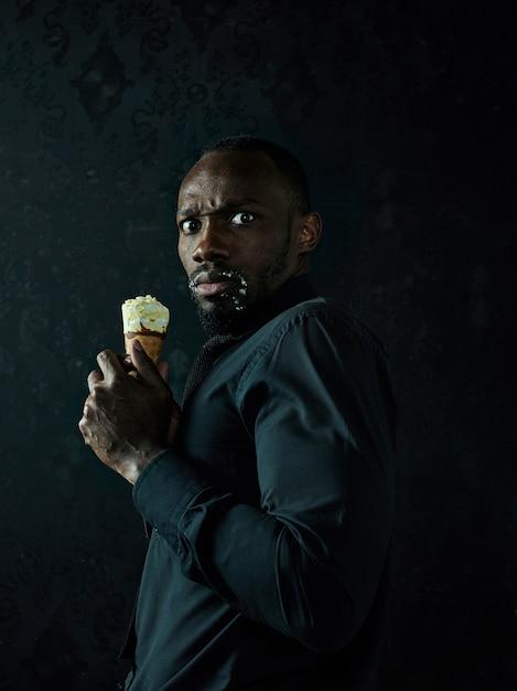 黒のスタジオの背景の上にアイスクリームを保持している悲しいアフロアメリカ人の肖像画 無料写真