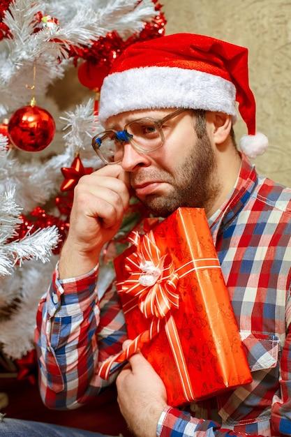 Портрет грустного человека с рождественским подарком в шляпе санты Premium Фотографии