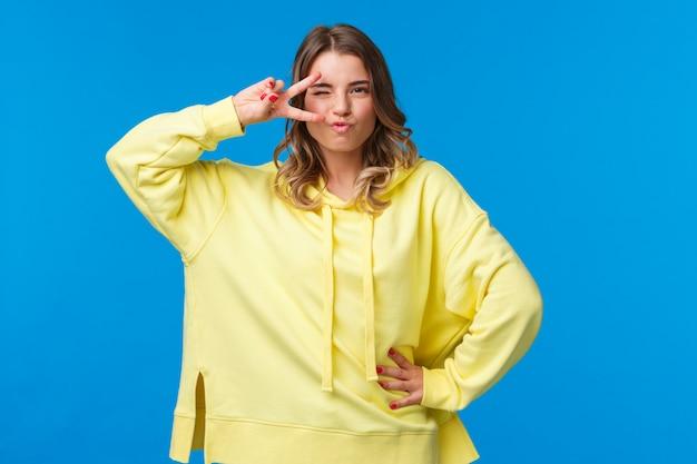 Портрет нахальной очаровательной белокурой кавказской женщины, танцующей дискотеку, показывающей знак мира возле глаз и выглядящей дерзкой и сексуальной камерой, стоящей в уверенной позе Premium Фотографии