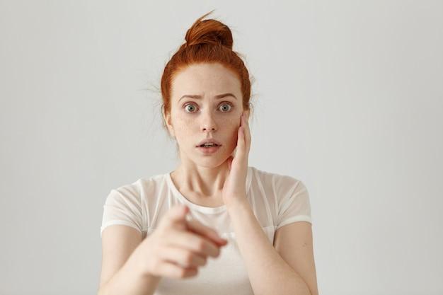 人差し指を指している間何かでおびえた恐ろしい恐ろしい表情をしている怖がっている虫目をした若い赤毛の女性の肖像画。危険、リスク、非難または認識 無料写真