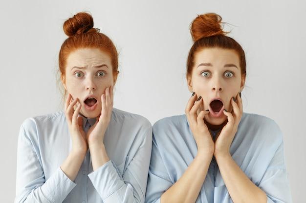 同じノットのヘアスタイルと正式なシャツを着て叫んでいる怖い無知な赤毛の女性会社員の肖像画 無料写真