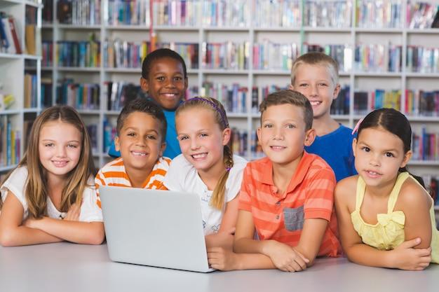 ライブラリでノートパソコンを使用している学校の子供たちの肖像画 Premium写真