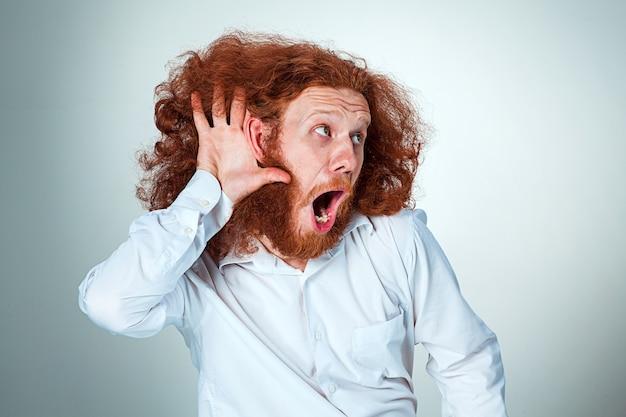 Портрет кричащего молодого человека с длинными рыжими волосами и шокирован выражением лица на сером фоне Бесплатные Фотографии