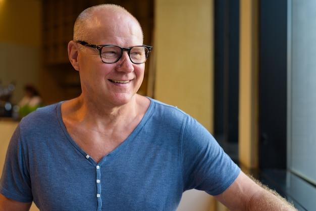 コーヒーショップの中でリラックスしたシニアハンサムなスカンジナビアの観光客の男の肖像画 Premium写真