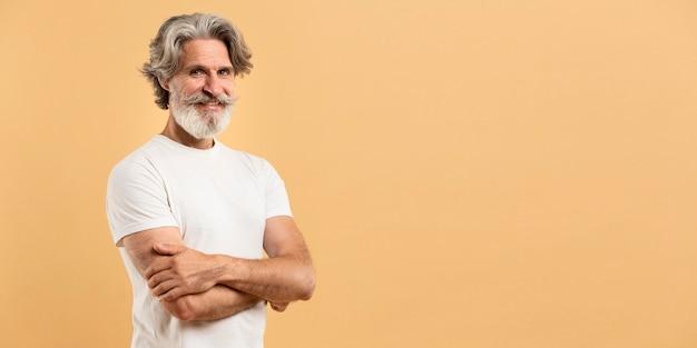 腕を交差し、コピースペースを浮かべて年配の男性の肖像画 Premium写真