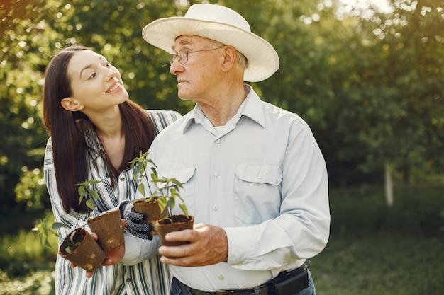 Портрет старшего мужчины в шляпе садоводства с внучкой Бесплатные Фотографии