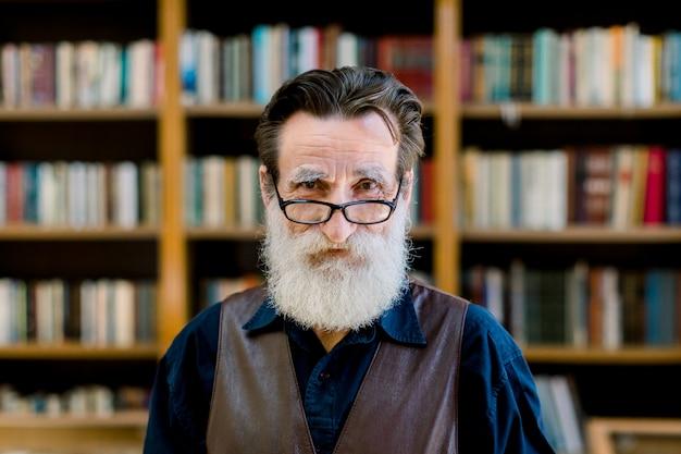 ひげと眼鏡、カメラ目線、本屋市場の背景の上に立って年配の男性の肖像画。ライブラリ、読書コンセプト Premium写真